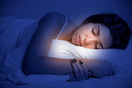 暗い寝室のベッドで寝ている女性