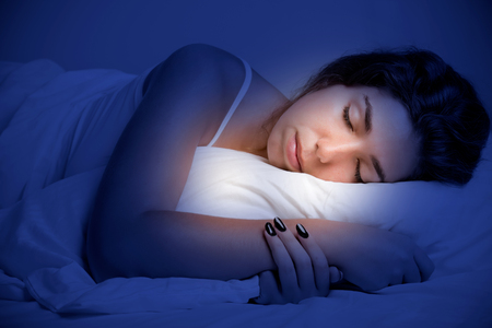 woman laying: Woman sleeping in a bed in a dark bedroom