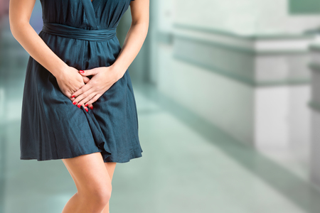 urination: Close up of a woman with hands holding her crotch in an emergency room