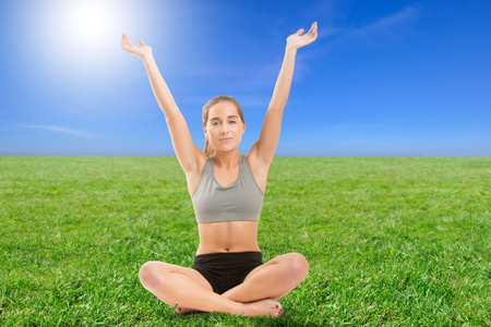 enlightment: Woman practicing  yoga with her arms in the air sitting on grass, backlit Stock Photo