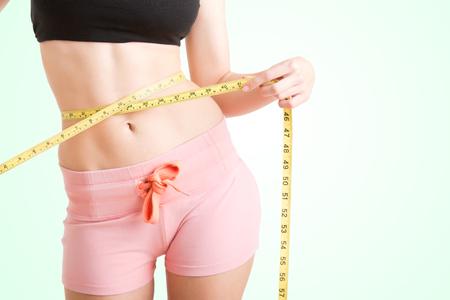 cintura: Mujer que mide su cintura con una cinta métrica amarilla, aislado en verde