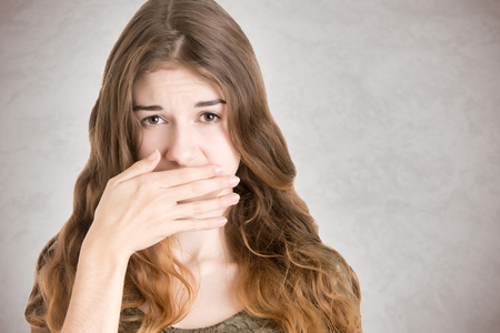 embarrassed: Female covering her mouth with her hand, isolated in white