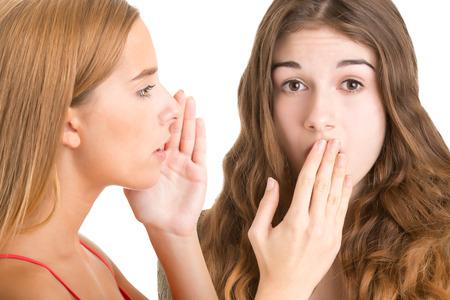 la boca: Mujer que dice un secreto a otra mujer, aislado en blanco