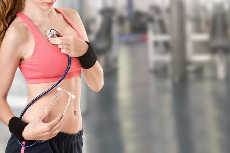 estetoscopio corazon: Concepto de una mujer deportiva examinar su estado de salud en un gimnasio