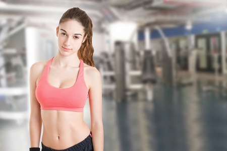 sport woman: Fit woman standing and relaxing after a workout in a gym