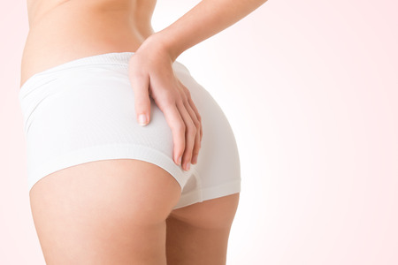 slim women: Closeup of woman examining her buttocks looking dor cellulite, isolated Stock Photo