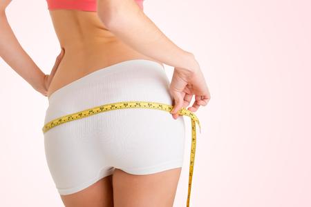 cinta metrica: Vista trasera de una mujer medir su cintura, aislado