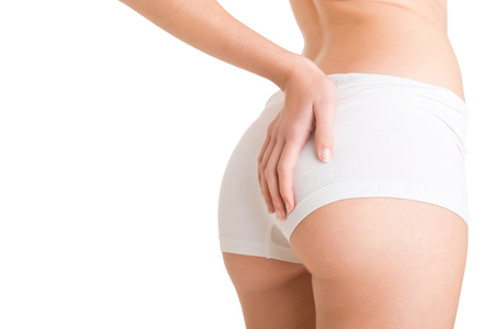 panties: Closeup of woman examining her buttocks looking dor cellulite, isolated in white