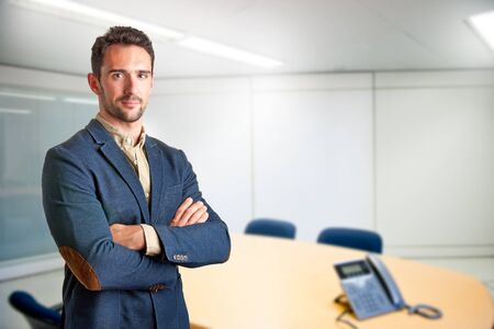 casual business man: Casual business man with arms crossed in a meeting room