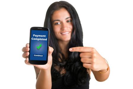 Il pagamento completato. Giovane donna che punta a un telefono cellulare e sorridente, isolato in bianco