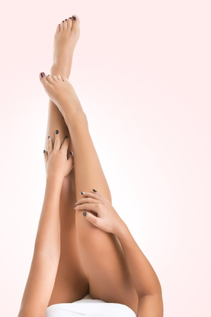 female legs: Beautifull and soft female legs standing up in the air, isolated in pink
