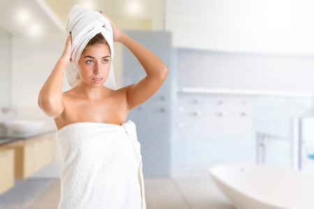 wrapped in a towel: Woman with a towel wrapped around her head, in a bathroom