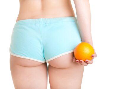 muslos: Mujer que sostiene una naranja contra sus muslos, aislado en blanco