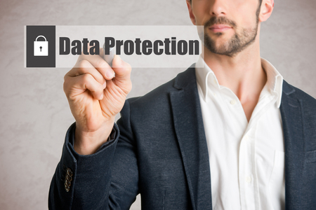 Man drawing data protection concept on glass, isolated in grey photo