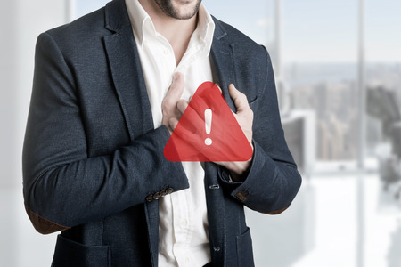 Man having a pain in the heart area, with a warning sign over him photo