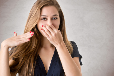 stink: Female covering her nose with her hand, isolated