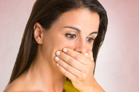 coy: Surprised woman covering her mouth, in a red background Stock Photo