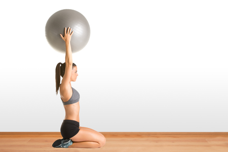 fit ball: Fit woman holding a pilates ball over her head, in a gym