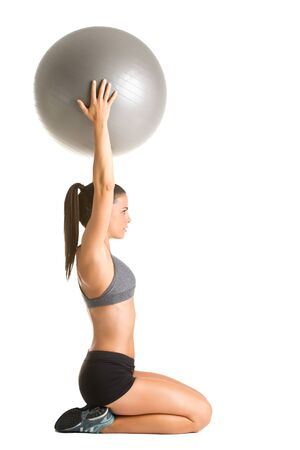 Fit woman holding a pilates ball over her head, isolated in white Stock Photo