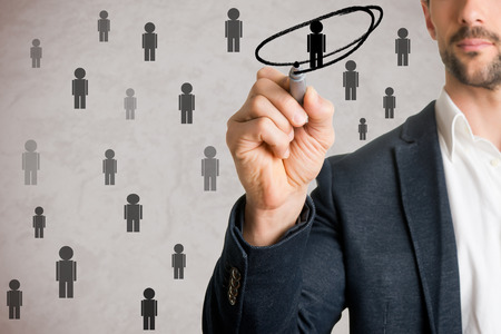 selection: Man drawing a circle around a person from a group. Human resources concept.
