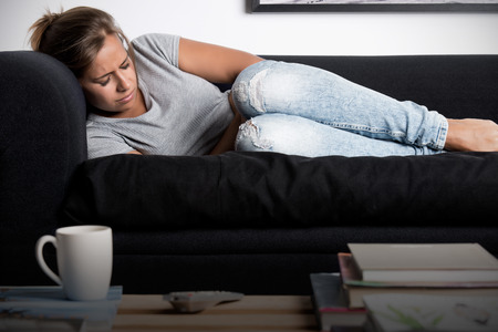 Woman lying on a couch with pain in her stomach Stockfoto