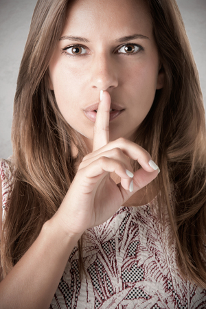 Closeup of a woman with her finger over her mouth, in a dark mood Stockfoto