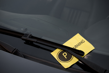notifying: Parking ticket on the windshield of a dark car Stock Photo