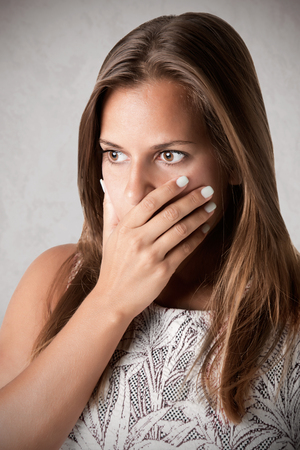 covering: Closeup of a concerned woman covering her mouth, in a dark mood