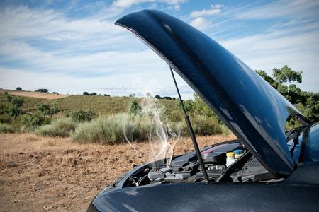 Close-up van een kapotte auto, motor geopend met rook, in een landelijk gebied