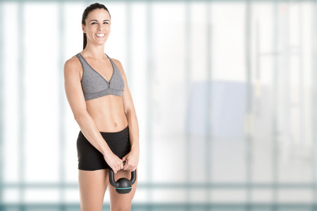 cardiovascular workout: Fit woman working out with a kettlebel and similingl, in a gym Stock Photo