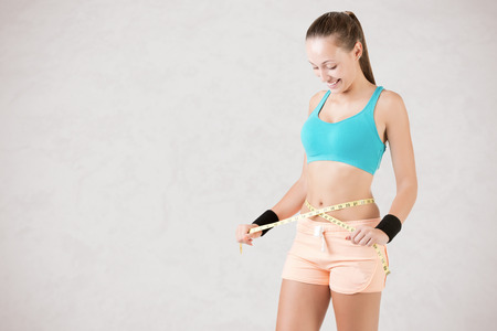 Woman measuring her waist with a yellow measuring tape, isolated in white Stock Photo