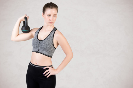 cardiovascular workout: Fit woman working out with a kettlebel and similingl, isolated in grey Stock Photo