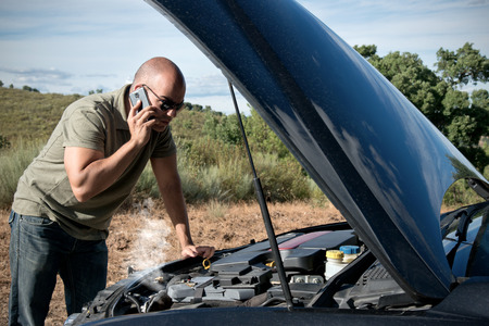 Close up of a broken down car, engine open and smoking, in a rural area and the driver looking at the engine