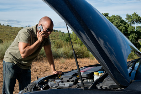 Close up of a broken down car, engine open, in a rural area and the driver looking at the engine