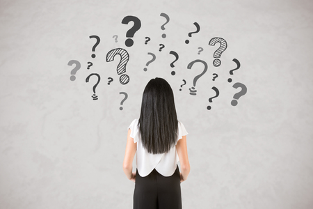 Backside of a businesswoman with question marks around her, isolated in white Stock Photo