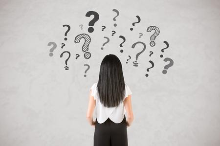 Rückseite einer Geschäftsfrau mit Fragezeichen rund um sie, isoliert in weiß Standard-Bild