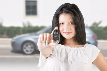 drivers license: Woman holding car keys with a car in the background Stock Photo