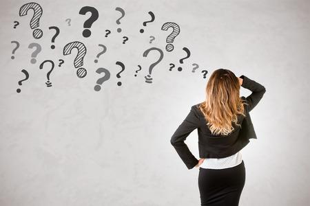 Achterkant van een zakenvrouw met vraagtekens rond haar, geïsoleerd in grijze Stockfoto
