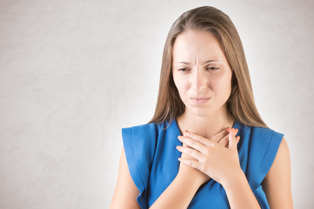 Woman with a sore throat holding her neck, isolated in grey Stock Photo