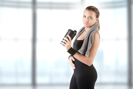 Woman resting with a towel around her neck after a fitness workout, in a gym