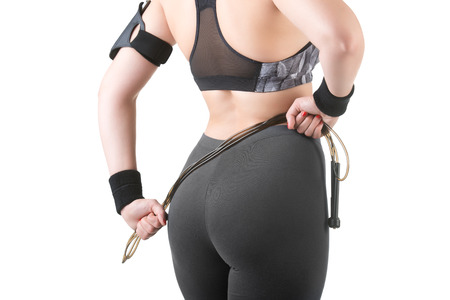 Back of sporty woman with a jumping rope, isolated in white