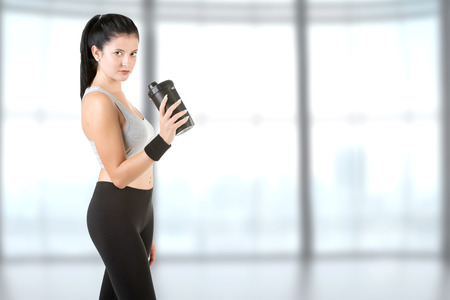 Woman resting with a towel around her neck after a fitness workout in a gym Stock Photo
