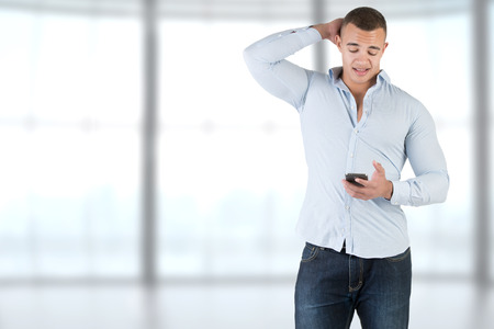 Young man using a smartphone and looking worried