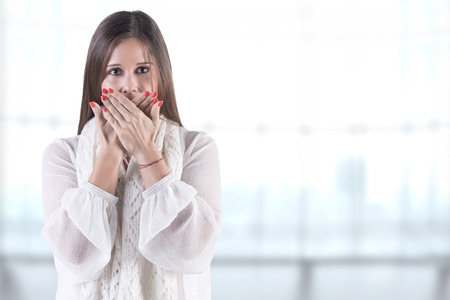 hysteria: Closeup of a concerned woman covering her mouth, in a blueish background Stock Photo