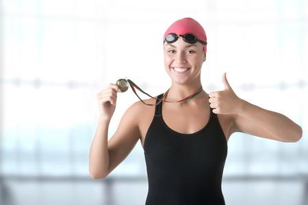 Female swimmer holding her medal after winning 免版税图像