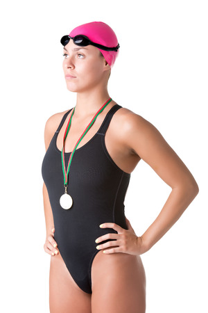Female swimmer holding her medal after winning, isolated in white
