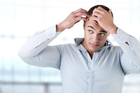 Man checking hairline, in a blue background Standard-Bild