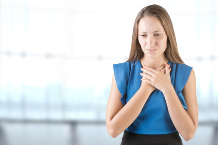 Woman with a sore throat holding her neck, in a blue background