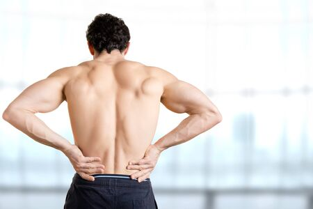 Male athlete with pain in his lower back, isolated in white. Red spot around painful area. Stock Photo