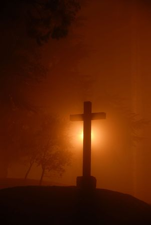 belive: small cross among fog in the dark night Stock Photo